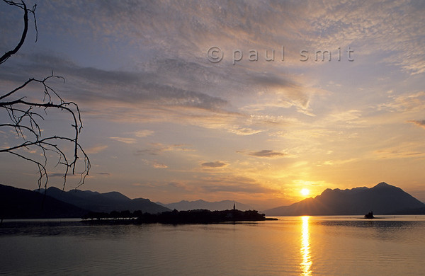 [ITALY.PIEMONTE 01644]  'Sunrise over Isola dei Pescatori.'  The only true village of the Borromeo Islands is situated on Isola dei Pescatori, the Fishermen's Island. Once only the fishermen from this island had the right to fish in the Lago Maggiore. Nowadays the inhabitants catch tourists in their fishrestaurants and souvenirshops. Between 11 am and 5 pm it's a kermis, but beyond and out of season it has lost little of its charm. Photo Paul Smit.