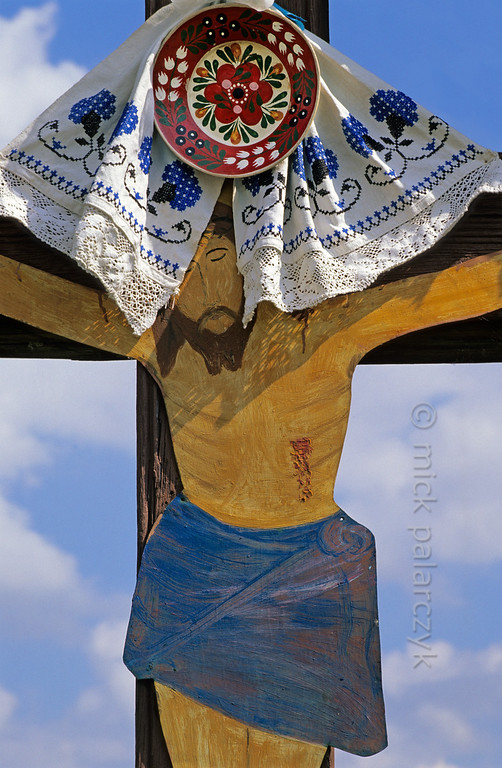 [ROMANIA.WEST 24.208] 'Adorned Christ.'  	In Petrani, south east of Orodea, this crucifix is decorated with specimens of local craft. Photo Mick Palarczyk.