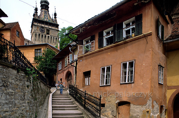 [ROMANIA.TRANSYLVA 24.153] 'Clock Tower in Sighisoara.'  	A narrow flight of stairs leeds to the old town of Sighisoara with its massive medieval Clock Tower. Photo Mick Palarczyk.