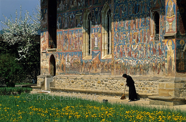 [ROMANIA.MOLDAVIA 23.916] 'Sweeping the yard.'  	A nun sweeps the grounds of Moldovita Monastery. Photo Mick Palarczyk.