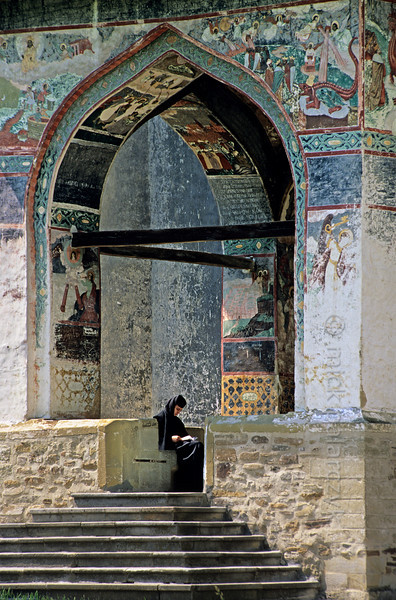 [ROMANIA.MOLDAVIA 24.085] 'Reading in the porch.'  Surrounded by colourful images this nun is reading in the southern porch of the Sucevita monastic church. Photo Mick Palarczyk.