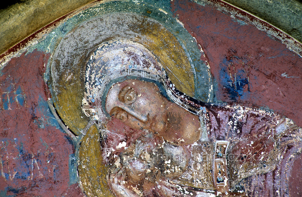 [ROMANIA.MOLDAVIA 24.016] 'Colourful Mary.'  A compassionate Mary arises from a riot of eroded colours above a porch in the church of the Humor Monastery. Photo Mick Palarczyk.