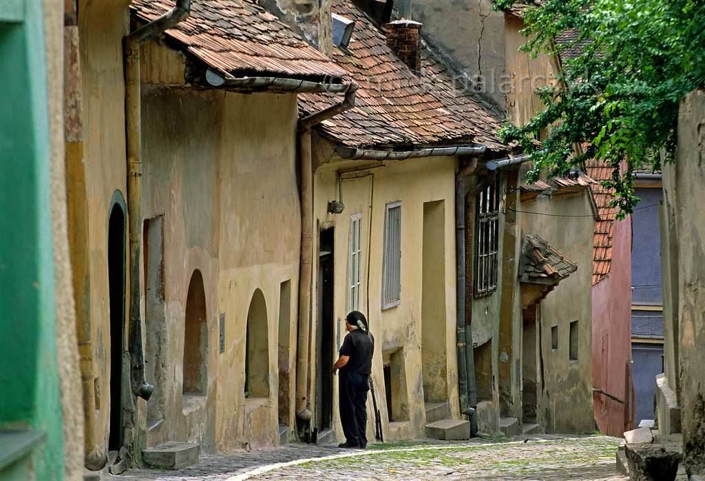 [ROMANIA.TRANSYLVA 24.147] 'Street in Sighisoara.'  Apart from being the birthplace of Vlad Tepes (Dracula) Sighisoara owes its charm to its brightly coloured old houses. Sighisoara is one of the Medieval fortified towns the Saxons built in southern Transylvania. Photo Mick Palarczyk.