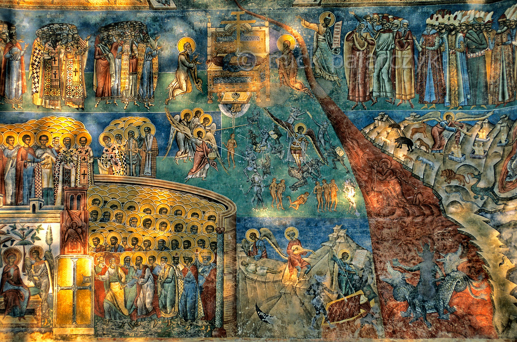 [ROMANIA.MOLDAVIA 23.991] 'Last Judgement.'  The last judgement scene at Voronet Monastery receives late afternoon sunlight filtering through surrounding trees. Hell breaks as a red chasm through the brilliant blue which was obtained from lapis lazuli. The fresco was painted in 1547. Photo Mick Palarczyk.