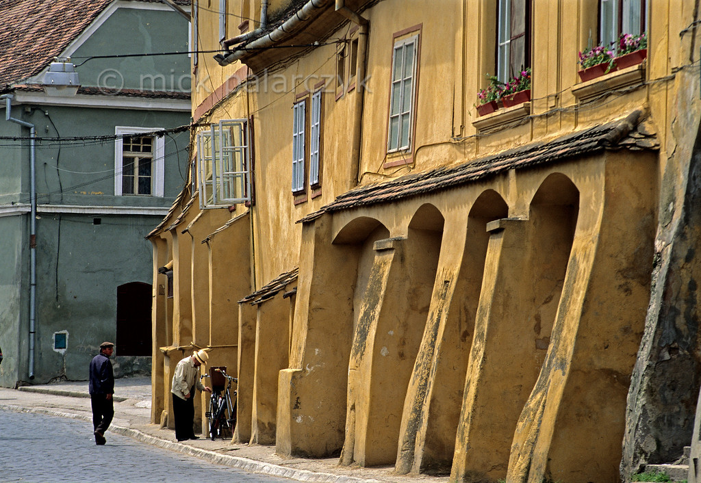 [ROMANIA.TRANSYLVA 24.144] 'Street in Sighisoara.'  Apart from being the birthplace of Vlad Tepes (Dracula) Sighisoara owes its charm to its brightly coloured old houses. Sighisoara is one of the Medieval fortified towns the Saxons built in southern Transylvania. Photo Mick Palarczyk.
