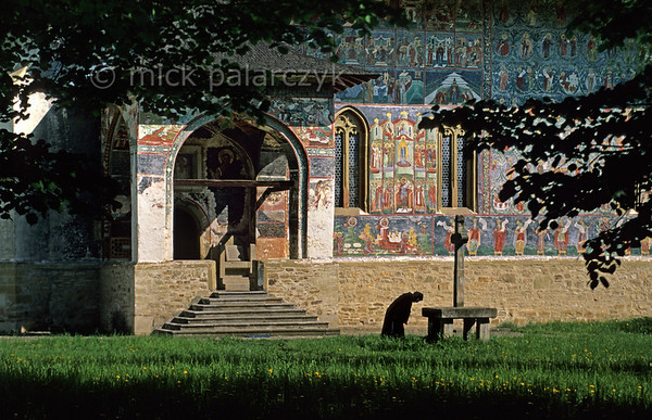 [ROMANIA.MOLDAVIA 24.088] 'Following mass in the garden.'  	While listening to the hymns of morning mass radiating from the south entrance of Sucevita's church, a nun bows in front of a stone cross in the monastic garden. Photo Mick Palarczyk.