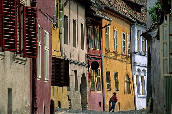 [ROMANIA.TRANSYLVA 24.167] 'Alley in Sighisoara.'  	Apart from being the birthplace of Vlad Tepes (Dracula) Sighisoara owes its charm to its brightly coloured old houses. Sighisoara is one of the Medieval fortified towns the Saxons built in southern Transylvania. Photo Mick Palarczyk.