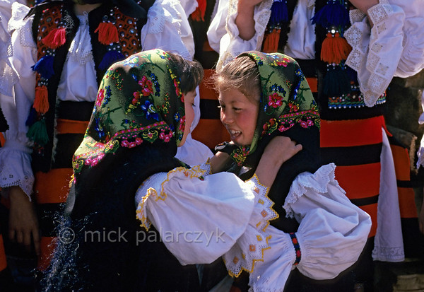 [ROMANIA.MARAMURES 23.872] 'Folkloristic excitement.'  During the 'Festival of the First Ploughman' in Hoteni two girls are checking each other's folkloristic dress. Photo Mick Palarczyk.