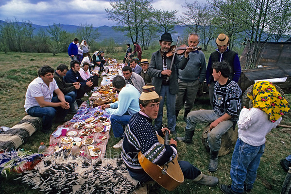 [ROMANIA.MARAMURES 23.865] 'Picnic with music.'  	At the end of the Stîna or 'Measuring of the Milk' festival, when all the sheep have been milked, the villagers of Hoteni enjoy an abundant meal in the mountain pastures above their village. (See also previous pictures.) Photo Mick Palarczyk.