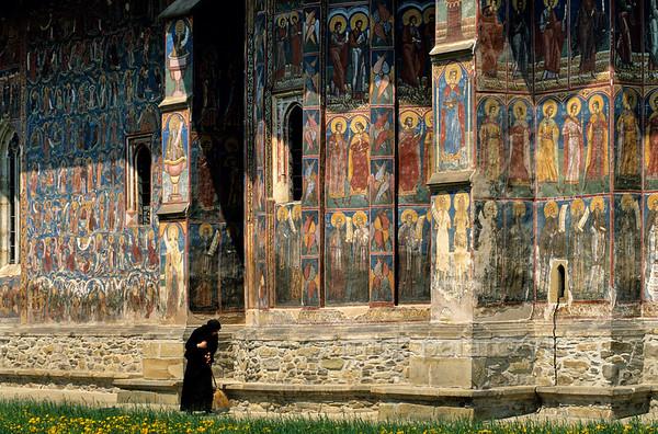 [ROMANIA.MOLDAVIA 23.934] 'Holy approval.'  	An crowd of holy men looks down approvingly on the mean work of a nun at the choir of Moldovita's monastery church. The frescoes were done in 1537 by Toma of Suceava. Photo Mick Palarczyk.
