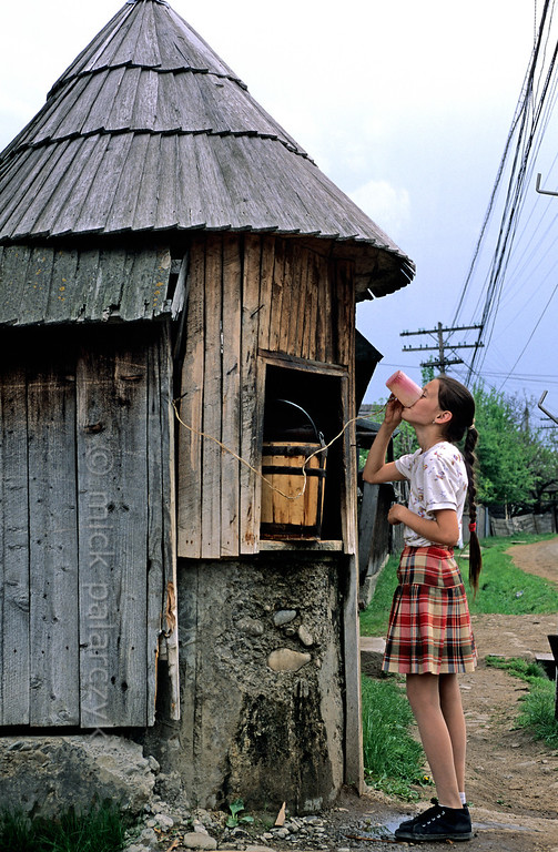[ROMANIA.MARAMURES 23.902] 'Thirsty girl.'  	A girl is drinking at a well in Bogdan Voda, a village in the Iza valley. Photo Mick Palarczyk.