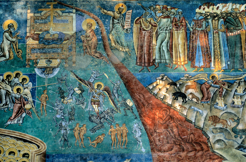 [ROMANIA.MOLDAVIA 23.994] 'Last Judgement.'  Hell breaks as a red chasm through brilliant blue in the last judgement scene at Voronet Monastery. On the right an angel sounds the last trumpet on an alpine horn. In response graves open and wild animals come bearing the limbs they have once devoured. On the left souls are being weighed. The fresco was painted in 1547. Photo Mick Palarczyk.