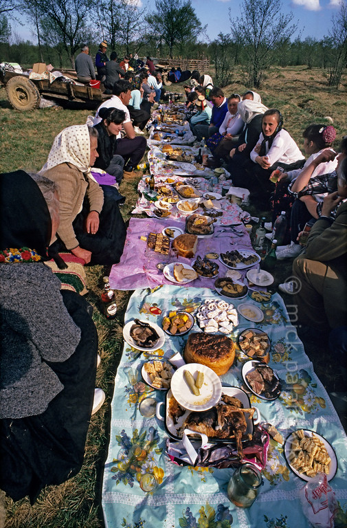 [ROMANIA.MARAMURES 23.863] 'Picnic after milking.'  	At the end of the Stîna or 'Measuring of the Milk' festival, when all the sheep have been milked, the villagers of Hoteni enjoy an abundant meal in the mountain pastures above their village. (See also previous pictures.) Photo Mick Palarczyk.