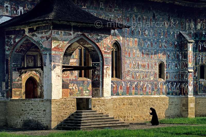 [ROMANIA.MOLDAVIA 24.056] 'Going to mass.'  In the Sucevita Monastery an old nun shuffles to the entrance of the Assumption Church to witness mass. The frescoes on the church were painted by the brothers Ioan and Sofronie of Suceava in 1595. Photo Mick Palarczyk.