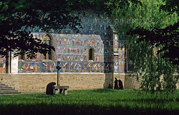 [ROMANIA.MOLDAVIA 24.097] 'Following mass in the garden.'  	While listening to the hymns of morning mass radiating from  Sucevita's monastic church, a nun bows in front of a stone cross while others are meditating near the church's south wall. The wall is covered by an impressive Tree of Jesse showing the ancestry of Jesus. The fresco was painted by the brothers Ioan and Sofronie of Suceava in 1595. Photo Mick Palarczyk.