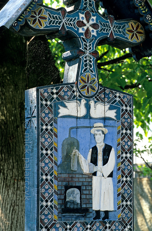 [ROMANIA.MARAMURES 23.739] 'The Merry Cemetery.'  At the Merry Cemetery (Cimitir vesel) of Sapînta local artist Stan Patras has decorated the crosses with scenes from the lives of the deceased. Here a man who is distilling alcohol. Photo Mick Palarczyk.
