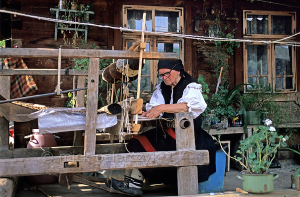 [ROMANIA.MARAMURES 23.752] 'Weaving on the verandah.'  	Working on an old loom in front of her house this inhabitant of Botiza village uses wool that has been coloured by plant extracts. Photo Mick Palarczyk.