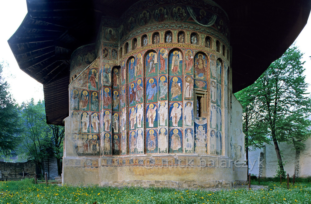 [ROMANIA.MOLDAVIA 23.982] 'Church with a hat.'  The frescoes of the Voronet monastic church are protected from the elements by a big mushroom-like roof. The monastery, which was founded in 1488, has been called the Sistine Chapel of the East. Photo Mick Palarczyk.