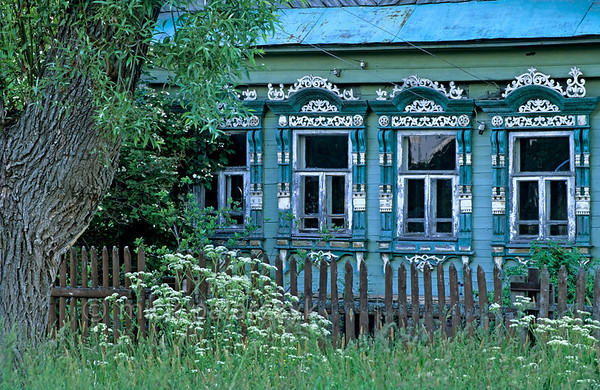 [RUSSIA.GOLDENRING 26.076] 'Turquoise izba .'  	A turquoise izba (traditional wooden peasant house) blends in with the grass and cow parsley in Nikitino village, 20 km southeast of Yaroslavl. Photo Mick Palarczyk.