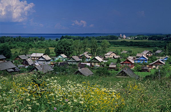 [RUSSIA.GOLDENRING 26.155] 'Izba's at Pereslavl.'  The Podgornaya neighbourhood of Pereslavl-Zalessky consists of a scattering of brightly coloured izba's. In the distance the sun shines on the Church of the Forty Saints, which is located at the spot where the Trubezh River enters Lake Pleshcheevo. Photo Mick Palarczyk.