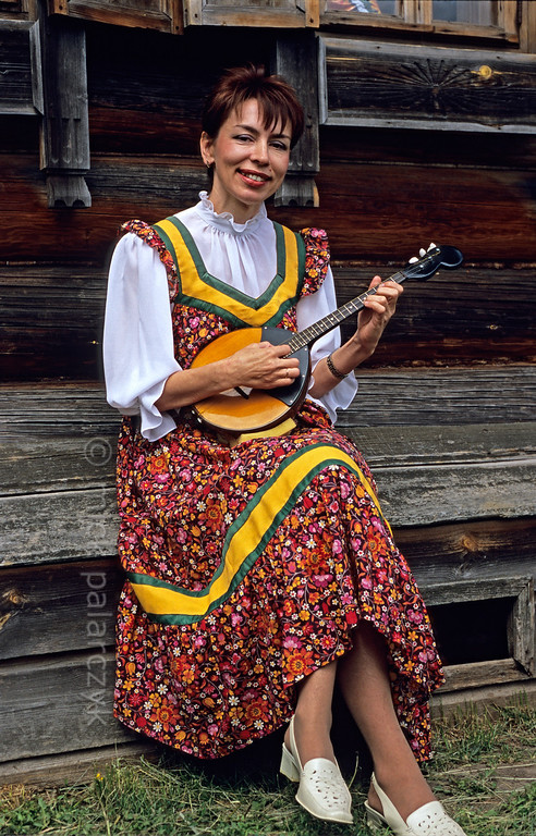 [RUSSIA.GOLDENRING 25.977] 'Playing a domra.'  At Suzdal a girl is playing a three-stringed domra during Troitsa (Whit Sunday) festivities. Photo Mick Palarczyk.