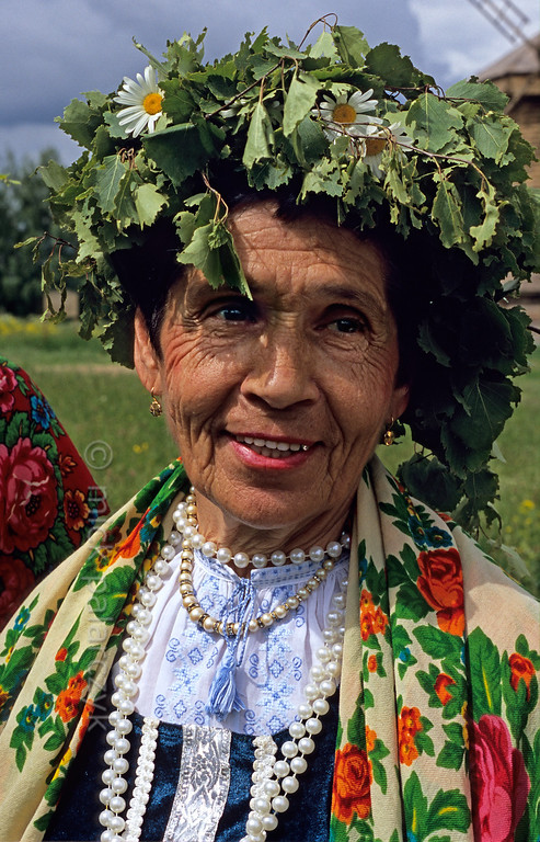[RUSSIA.GOLDENRING 25.973] 'Troitsa festivities.'  	During Troitsa (Whit Sunday) festivities in Suzdal a woman wears a wreath of birch twigs intertwined with marguerites. The birch personifies the renewal of life in spring. Photo Mick Palarczyk.