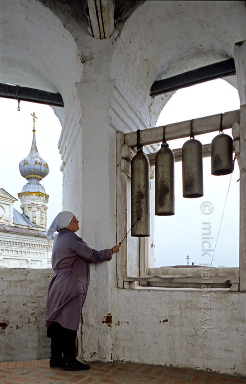 [RUSSIA.GOLDENRING 26.042] 'Ringing gas-canisters.'  	At the Monastery of the Archangel Michael in Yuryev-Polskoi, a bell-ringer in the monastery's tower strikes bells that are made of old gas-canisters. Photo Mick Palarczyk.