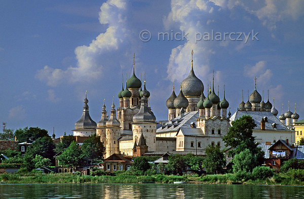 [RUSSIA.GOLDENRING 26.145] 'Rostov's kremlin.'  The fairy tale of Rostov-Veliky's kremlin is best appreciated from a boat on Lake Nero. The two highest structures are the Gate-Church of St. John (with green domes) and the Assumption (Uspensky) Cathedral (with gray domes). Although founded in the 12th century nearly all the buildings in the kremlin date from the 16th and 17th centuries. Photo Mick Palarczyk.