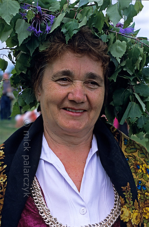 [RUSSIA.GOLDENRING 25.968] 'Troitsa festivities.'  	During Troitsa (Whit Sunday) festivities in Suzdal a woman wears a wreath of birch twigs intertwined with cornflowers. The birch personifies the renewal of life in spring. Photo Mick Palarczyk.