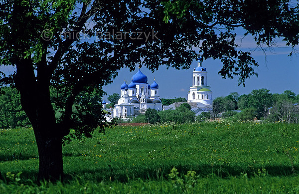 [RUSSIA.GOLDENRING 25.919] 'Bogolyubovo Monastery.'  	Seen from the meadows along the Klyazma River, the Assumption (Uspenski) Cathedral (1866) and bell tower (1841) of the  monastery at Bogolyubovo shimmer as a blue and white apparition above the horizon. Photo Mick Palarczyk.