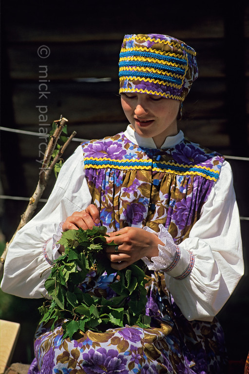 [RUSSIA.GOLDENRING 25.962] 'Twining a wreath.'  During Troitsa (Whit Sunday) festivities in Suzdal a girl is twining a wreath of birch twigs which she will wear during the day. Following an old custom, in the evening the wreath should be thrown in the river. The girl would mary on the side of the river, where the wreath landed. Photo Mick Palarczyk.