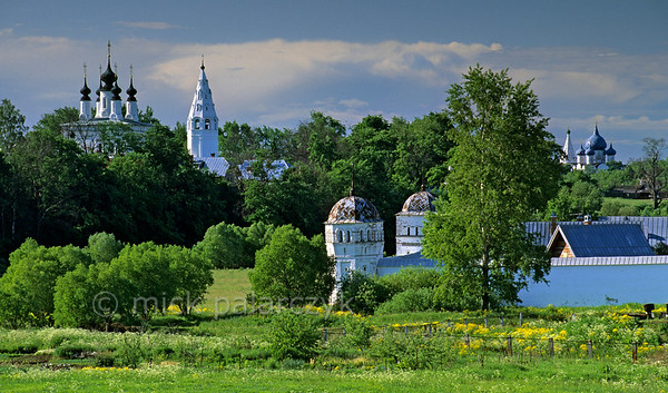 [RUSSIA.GOLDENRING 25.997] 'Kamenka valley.'  Looking in southerly direction along Suzdal's Kamenka valley the church and bell-tower of the Alexandrovski Convent can be seen on the high left bank of the river. To the right shimmer the blue domes of the Kremlin Cathedral. The foreground is taken up by the the towers and wall of the Intercession (Pokrovski) Convent. Photo Mick Palarczyk.