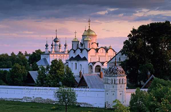 [RUSSIA.GOLDENRING 25.948] 'Convent Cathedral.'  	The golden domes and white walls of the Cathedral in Suzdal's Intercession (Pokrovski) Convent catch the last rays of a setting sun. Left of the Cathedral the five gray onion domes of the Church of St. Peter and Paul can be seen. It lies just outside the southern wall of the convent. Photo Mick Palarczyk.