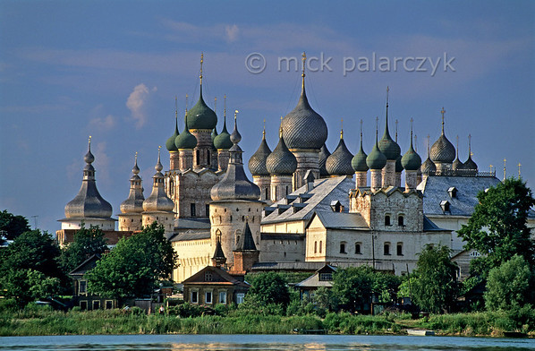 [RUSSIA.GOLDENRING 26.149] 'Rostov's kremlin.'  	The fairy tale of Rostov-Veliky's kremlin is best appreciated from a boat on Lake Nero. The two highest structures are the Gate-Church of St. John (with green domes) and the Assumption (Uspensky) Cathedral (with gray domes). Although founded in the 12th century nearly all the buildings in the kremlin date from the 16th and 17th centuries. Photo Mick Palarczyk.