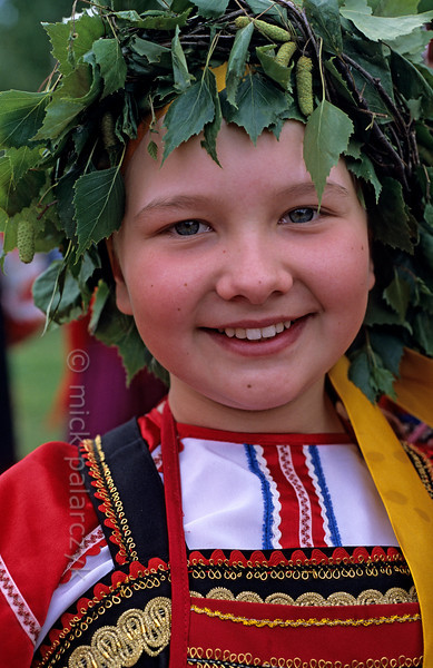 [RUSSIA.GOLDENRING 25.989] 'Girl with wreath.'  	During Troitsa (Whit Sunday) festivities in Suzdal a girl in traditional dress wears a wreath of birch twigs. The birch personifies the renewal of life in spring. Photo Mick Palarczyk.