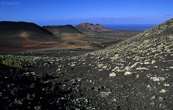 [SPAIN.CAN.LANZAROTE 9316] 'Main volcano chain.'  The main chain of volcanoes in the Timanfaya national park lie on a straight line, seen here in the distance. The furthest volcano is El Mirador and the one at left is Montaña de Timanfaya, Lanzarote's highest. Photo Paul Smit.