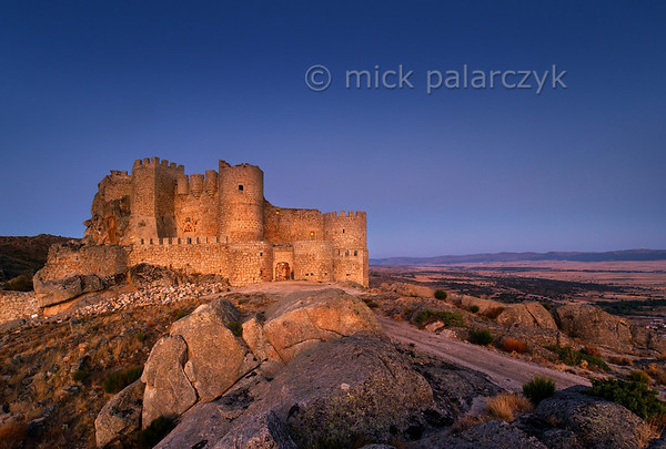 [SPAIN.CLEON 28607] 'Aunqueospese Castle before sunrise.'  Aunqueospese Castle, near the village of Mironcillo, sits on a rocky hill in the Sierra de la Paramera, commanding the plains of Ávila. Building of the castle started in 1490. We see it here, lighting up in the glow of the eastern sky, just before sunrise. Photo Mick Palarczyk.