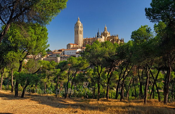 [SPAIN.CLEON 28587] 'Segovia's cathedral seen from the Clamores valley.'  	From under the pines in the valley of the Clamores river there is a superb view of Segovia's cathedral. Construction of the cathedral started as late as 1525, making it the last major Gothic building in Spain. Photo Mick Palarczyk.
