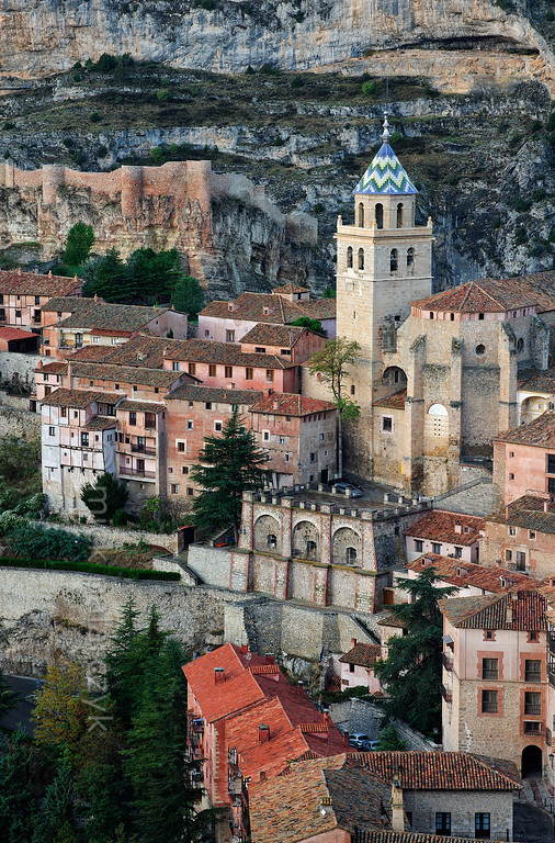 [SPAIN.ARAGON 28681] 'Albarracín and its castle.'  	Albarracín is a beautifully preserved medieval town in the canyon of the Guadalaviar river in the southwest of Teruel province. Its castle (in the upper left part of the picture) is a Moorish fort (alcazaba) of the 10th century, built during the caliphate of Córdoba. In the 11th century the town became the capital of a taifa, an independent Muslim state ruled by the Banu Razin dynasty, whose family name would lend the town its name (Sahla Banu Razin). From 1170 till 1285 it was the capital of the small independent Christian kingdom of the Azagra family. Its medieval cathedral was remodeled in the 16th and 18th centuries. Photo. Mick Palarczyk.