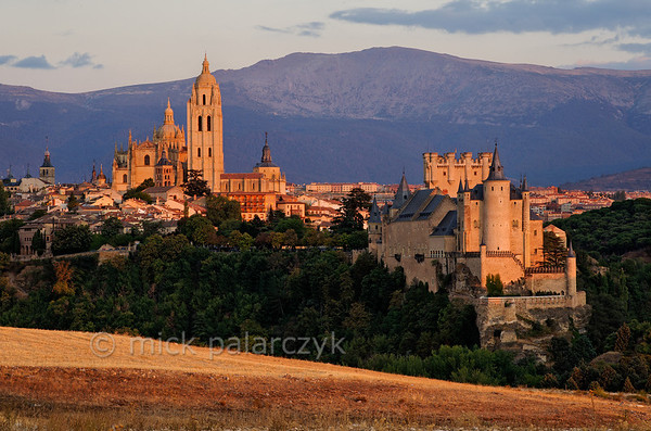 [SPAIN.CLEON 28574] 'Segovia seen from the west.'   The last rays of the evening sun highlight the cathedral and Alcazar of Segovia against the backdrop of the Sierra de Guadarama. Photo Mick Palarczyk.