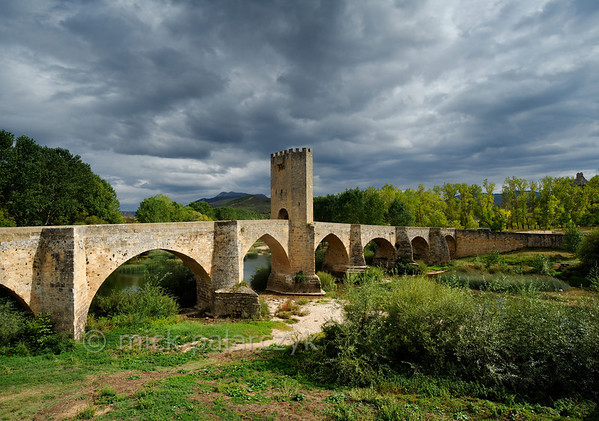 [SPAIN.CLEON 28624] 'Medieval bridge at Frías.'  	The medieval bridge at Frías (Burgos province) crosses the Ebro with nine arches over a distance of 143 meters. It was built on earlier Roman foundations. The central defense tower, where toll was levied,  was added in the 14th century. Photo Mick Palarczyk.