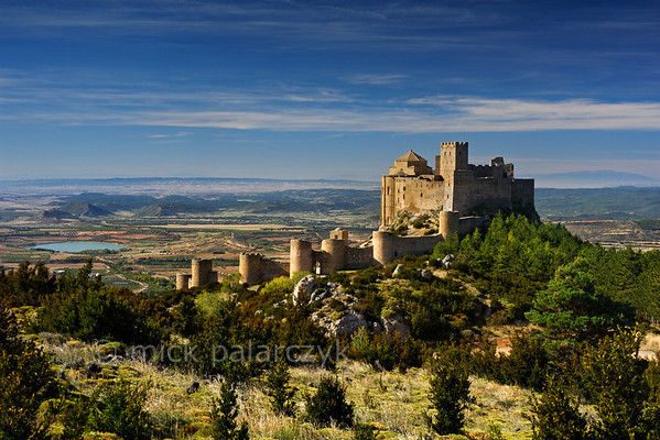 [SPAIN.ARAGON 28702] 'Castle of Loarre.'  	The castle of Loarre crowns a great outcrop of rock that juts out of the Pyrenean foothills north of the city of Huesca. The central core of the castle was built in 1020-1035 by king Sancho III of Navarra (and ruler of the emergent kingdom of Aragon) to protect his territory from the Moors in Huesca. In 1071 king Sancho Ramirez of Aragon extended the castle with a fortified (Augustinian) monastery and church. The outer wall with circular defense towers was added in 1287. The castle was abandoned in the 15th century and has survived the centuries relatively untouched due to its inaccessibility. Photo Mick Palarczyk.