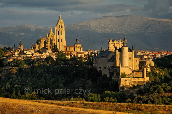 [SPAIN.CLEON 28573] 'Segovia seen from the west.'  The evening sun highlights the cathedral and Alcazar of Segovia against the backdrop of the Sierra de Guadarama. Photo Mick Palarczyk.