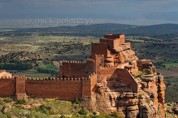 [SPAIN.ARAGON 28696] 'Castle of Peracense.'  	The castle of Peracense sits atop a remote crag of red sandstone in the Sierra de Almohaja (Teruel province). It is first mentioned in 1284 when King Pedro III of Aragon used it as a base for capturing the independent Christian kingdom of Azagra whose capital Albarracín lies 25 km to the south. In the 14th century it played a role in the wars between Castile and Aragon because its location commands the gorge through which invading armies could pass between the two kingdoms. Photo Mick Palarczyk.