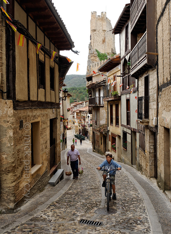 [SPAIN.CLEON 28622] 'Alley and castle in Frías.'  The narrow streets in medieval Frías (Burgos province) are lined with timber framed houses. Towering above them is the keep of Frias Castle. The history of the castle dates back to the 10th century when it was of great strategic value for the defense against Moorish forces. The present structure is the result of building phases of the 12th till the 16th century. Photo Mick Palarczyk.