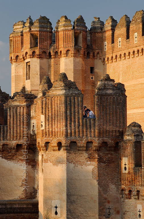 [SPAIN.CLEON 28594] 'Turrets of Coca Castle.'  	Two visitors linger in a turret of the eastern wall of Coca Castle (Segovia province). It was built in the second half of the 15th century by Alonso de Fonseca, the powerful archbishop of Seville and bishop of Ávila. The fortress is a beautiful example of the so-called Mudejar style: a mixture of Moorish and Christian style elements. It is brick-built because this was the principal material used by the Moorish master builders. Brick was the material with which it was possible to create the multitude of turret forms and details in the flat surfaces. Photo Mick Palarczyk.