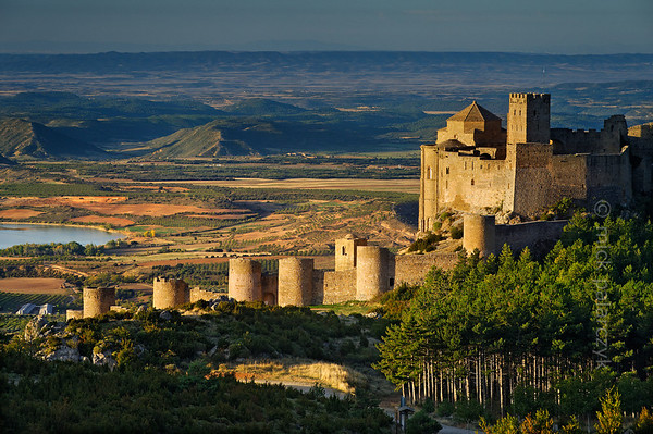 [SPAIN.ARAGON 28700] 'Castle of Loarre.'  	The castle of Loarre crowns a great outcrop of rock that juts out of the Pyrenean foothills north of the city of Huesca. The central core of the castle was built in 1020-1035 by king Sancho III of Navarra (and ruler of the emergent kingdom of Aragon) to protect his territory from the Moors in Huesca. In 1071 king Sancho Ramirez of Aragon extended the castle with a fortified (Augustinian) monastery and church. The outer wall with circular defense towers was added in 1287. The castle was abandoned in the 15th century and has survived the centuries relatively untouched due to its inaccessibility. Photo Mick Palarczyk.