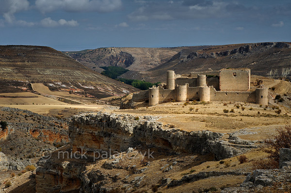 [SPAIN.CLEON 28652] 'Caracena Castle seen from the south.'  In the remote mountains of southern Soria province the ruined castle of Caracena balances on the edge of a gorge that empties into the Rio Caracena. The castle originally dates from the 12th century but was completely rebuilt in 15th. Photo Mick Palarczyk.