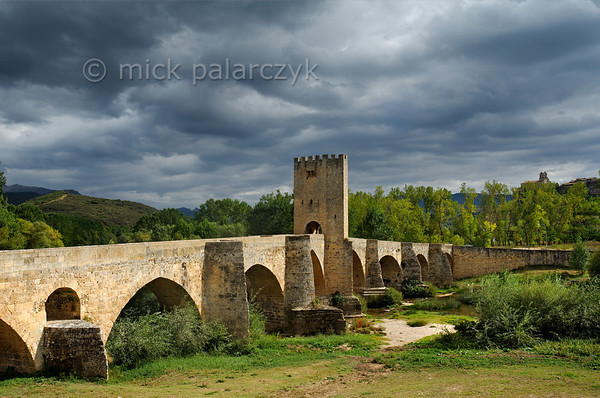 [SPAIN.CLEON 28623] 'Medieval bridge at Frías.'  The medieval bridge at Frías (Burgos province) crosses the Ebro with nine arches over a distance of 143 meters. It was built on earlier Roman foundations. The central defense tower, where toll was levied,  was added in the 14th century. Photo Mick Palarczyk.