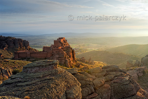 [SPAIN.ARAGON 28693] 'Castle of Peracense.'  	The castle of Peracense sits atop a remote crag of red sandstone in the Sierra de Almohaja (Teruel province). It is first mentioned in 1284 when King Pedro III of Aragon used it as a base for capturing the independent Christian kingdom of Azagra whose capital Albarracín lies 25 km to the south. In the 14th century it played a role in the wars between Castile and Aragon because its location commands the gorge through which invading armies could pass between the two kingdoms. Photo Mick Palarczyk.